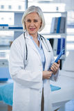 Portrait of a smiling female doctor holding clipboard Stock Images