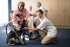 Portrait of smiling female doctor kneeling by disabled senior man stroking puppy Stock Photo