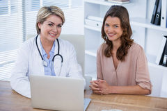 Portrait of smiling female doctor and patient sitting at desk Royalty Free Stock Photo