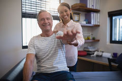 Portrait of smiling female doctor and senior male patient with arms raised Stock Image