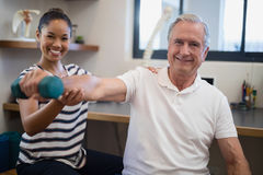 Portrait of smiling female doctor with senior male patient holding dumbbell Stock Image