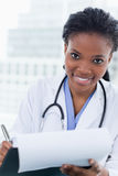 Portrait of a smiling female doctor signing a document Stock Photography