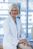 Portrait of a smiling female doctor sitting at desk Stock Photo