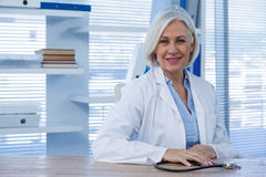 Portrait of a smiling female doctor sitting at desk Royalty Free Stock Photography