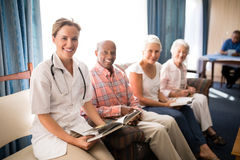 Portrait of smiling female doctor sitting with senior man and women on sofa Royalty Free Stock Photos