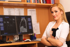 Portrait of a smiling female doctor sitting at work desk Stock Photos