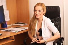 Portrait of a smiling female doctor sitting at work desk Royalty Free Stock Photos