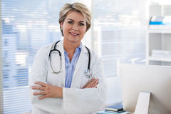 Portrait of a smiling female doctor standing with arms crossed Royalty Free Stock Photography