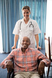 Portrait of smiling female doctor standing with disabled senior man sitting on wheelchair Royalty Free Stock Image