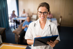 Portrait of smiling female doctor standing with file Stock Photos