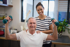 Portrait of smiling female doctor standing with male patient lifting dumbbells Stock Photography
