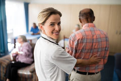 Portrait of smiling female doctor standing with senior man Stock Photo