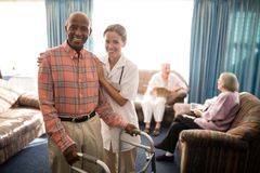 Portrait of smiling female doctor standing by senior man with walker against window Royalty Free Stock Images