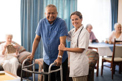 Portrait of smiling female doctor standing by senior man with walker Royalty Free Stock Photography