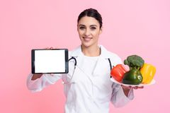 Portrait of smiling female doctor with stethoscope holding plate of vegetables and tablet isolated. royalty free stock image