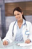 Portrait of smiling female doctor. Working at desk in office, using laptop, smiling Stock Photos