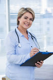 Portrait of a smiling female doctor writing on clipboard Stock Photos