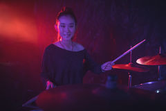 Portrait of smiling female drummer playing drum kit in nightclub Royalty Free Stock Photo