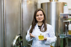 Portrait of smiling female engineer holding perfume oil bottle Stock Photography