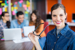 Portrait of smiling female executive standing with spectacles Royalty Free Stock Photos