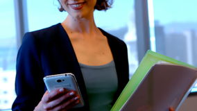 Smiling female executive using mobile phone in office. Portrait of smiling female executive using mobile phone in office stock video footage