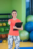 Portrait of smiling female fitness instructor writing in clipboard while standing in gym Stock Photography