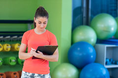 Portrait of smiling female fitness instructor writing in clipboard while standing in gym.  Royalty Free Stock Photos