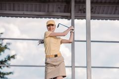portrait of smiling female golf player in cap with golf club