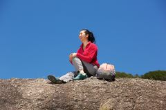 Smiling female hiker sitting on rock and enjoying the view Stock Image