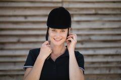 Portrait of smiling female jockey adjusting sports helmet Stock Image