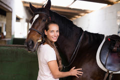 Portrait of smiling female jockey standing by horse. In stable Royalty Free Stock Image