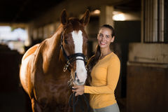 Portrait of smiling female jockey standing by horse. In stable Stock Photography