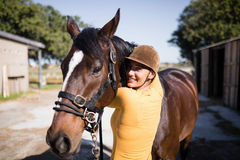 Portrait of smiling female jockey stroking horse. At stable Stock Photo