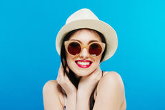 Portrait of Smiling Female Model in Fashion Sunglasses and Summer Hat on Blue Background. royalty free stock photos