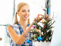Portrait of smiling female office worker with Christmas tree Royalty Free Stock Photo