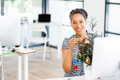 Portrait of smiling female office worker with Christmas tree Stock Photos