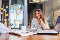Portrait of smiling female office worker writing looking at camera sitting at conference room during the meeting Stock Photography
