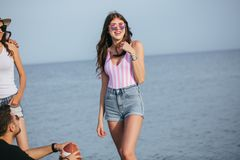 Young slim beautiful woman on beach, playful, dancing, summer vacation, having fun, positive mood, happy. Portrait of smiling female sea. Happy women standing at royalty free stock photography