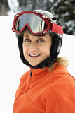 Portrait of Smiling Female Skier. Closeup of smiling female skier wearing red goggles and orange ski jacket. Vertical shot Stock Image