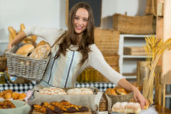 Portrait of smiling female staff holding breads in wicker basket at counter stock photos