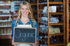 Portrait of smiling female staff holding a organic sign board Stock Photo