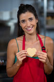 Portrait of smiling female staff showing heart shape cookie at counter. In bake shop royalty free stock images