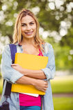 Portrait of smiling female student carrying bag and file Royalty Free Stock Photos