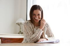 Smiling female student working at home. Portrait of smiling female student working at home Royalty Free Stock Image