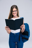 Portrait of a smiling female teenager reading book. Portrait of a smiling female teenager with backpack reading book isolated on a white background Stock Photos