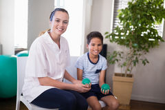 Portrait of smiling female therapist and boy holding stress balls. In hospital ward Royalty Free Stock Photography