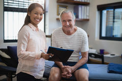 Portrait of smiling female therapist standing with clipboard by senior male patient sitting on bed Stock Photo