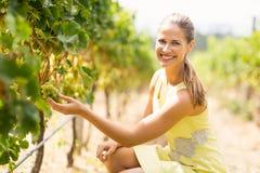 Portrait of smiling female vintner inspecting grapes Stock Photo
