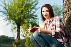 Portrait of smiling female writing on her journal or diary Royalty Free Stock Image