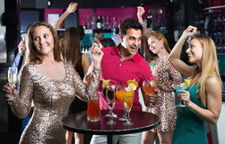 Portrait of smiling females and males having fun in the bar. Portrait of happy positive smiling females and males having fun in the bar Royalty Free Stock Image